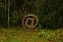 Сreative email symbol. Wooden element on a grass royalty free stock images